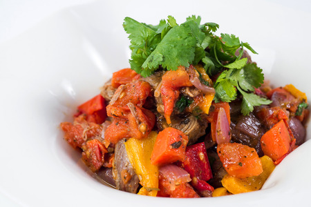 Meat in tomato sauce with vegetables close up in a pot. White background