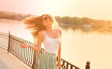 Portrait of beautiful woman having fun in city park. Stock Photo