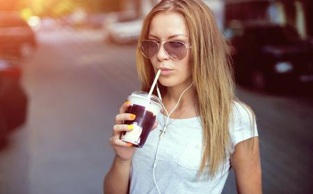 shake off: pretty girl with milk shake listening music on the street. Sunset Stock Photo