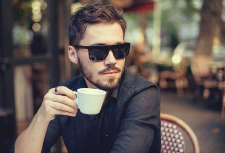 Moderne zakenman drinken koffie bij coffee shop op de zonsondergang. Stockfoto