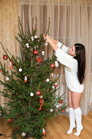 decorating christmas tree: Beautiful girl Decorating Christmas tree on bright background.