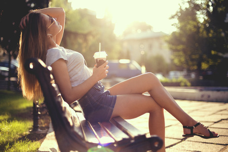 pretty smiling girl with milk shake sitting on bench