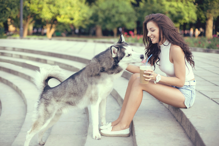 blue eye husky: girl drinking ice coffee and playing with her husky dog in the park.