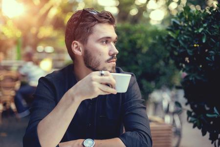 Cutie man met een kopje koffie kijken naar de mobiele telefoon buitenshuis. Stockfoto