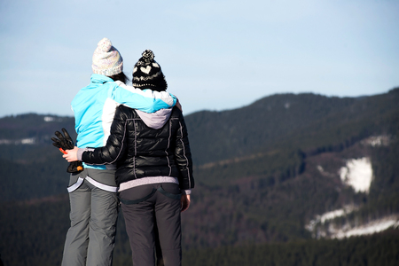 wintertime: girls enjoying mountain view together in wintertime.