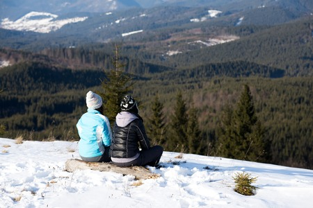 wintertime: girls enjoying mountain view together in wintertime Stock Photo