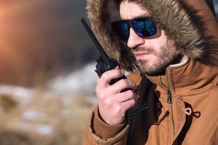 talkie: Male hiker using walkie talkie against mountain peaks.