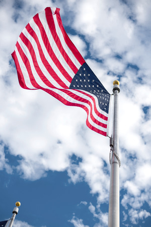 red flag up: American flags winding on the blue sky.