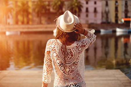 Young woman in hat and cute summer dress standing on the pier with peaceful town scenery, looking at sunset. Standard-Bild