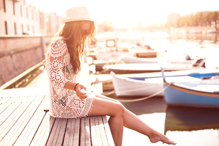 Young woman in hat and cute summer dress standing on the pier with peaceful town scenery, looking at sunset. 免版税图像