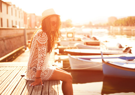 peaceful: Young woman in hat and cute summer dress standing on the pier with peaceful town scenery, looking at sunset. Stock Photo