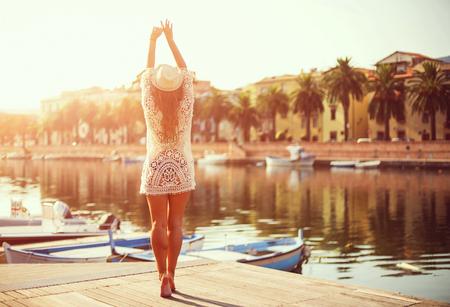 Jonge vrouw in hoed en leuke zomer jurk staande op de pier met rustige stad landschap, kijkend naar de zonsondergang. Stockfoto