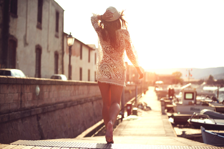 Young woman in hat and cute summer dress standing on the pier with peaceful town scenery, looking at sunset. Stock Photo