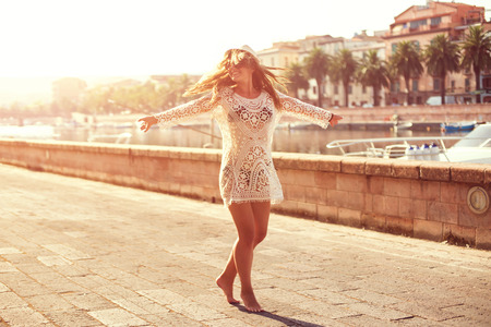 Young woman in hat and cute summer dress spinning on the road, with peaceful town scenery, looking at sunset. Imagens