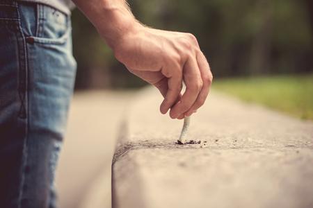 extinguish: Hand of a young man extinguish cigarette.