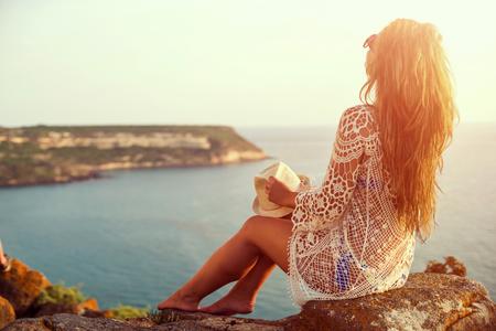 cielo y mar: Mujer joven en el sombrero y vestido lindo del verano de pie sobre la piedra, mirando la puesta de sol sobre el mar. Foto de archivo
