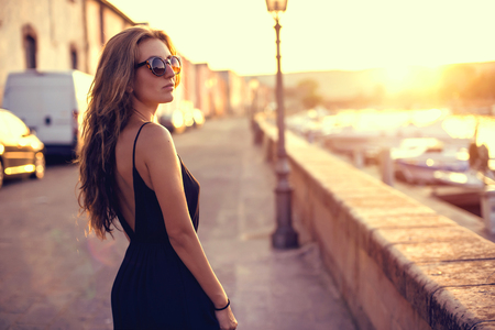 Young pretty woman in black dress, sunglasses and white sneakers at sunset in Italy Stock Photo