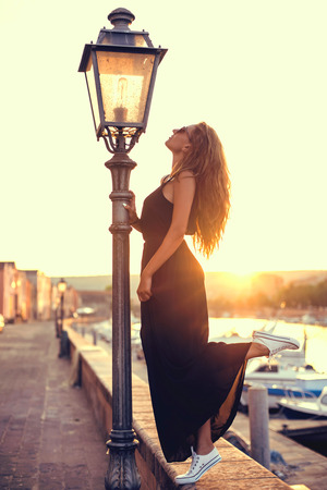 habiliment: Young pretty woman in black dress, sunglasses and white sneakers at sunset in Italy Stock Photo