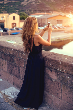 habiliment: Young pretty woman in black dress taking pictures on the smartphone. Sardinia. Italy