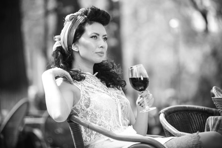 Beautiful young girl with glass of red wine alone in a street cafe.