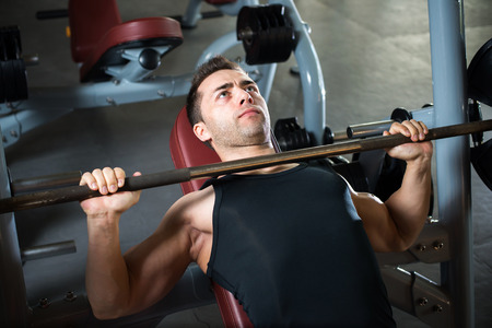 brawny: very power athletic guy , execute exercise press with weight, in sport hall.