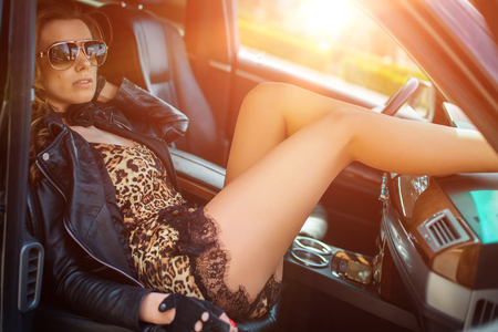 waxed legs: portrait of young beautiful woman sitting in the car.
