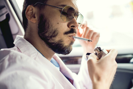Young businessman lighting up a cigarette with a lighter in his cupped hands puffing smoke. Stock Photo