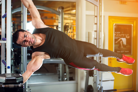 musculation: very power athletic guy , execute exercise in sport hall. Stock Photo
