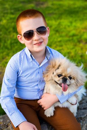 Baby boy lovingly embraces his pet dog. Stock Photo