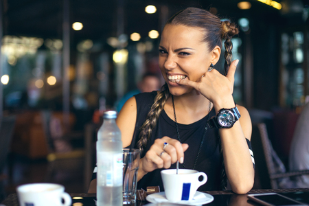 Woman with pigtails drinking coffee in trendy cafe