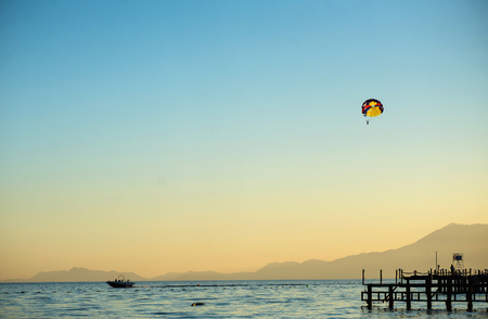 Sunset over the sea and suddenly emerging out of the blue paraglider. Stock Photo