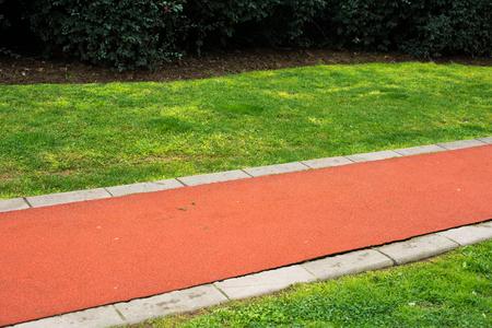 beautiful red street on the green grass background Standard-Bild