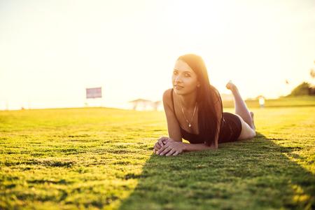 happy beautiful woman in bikini on the green grass on sunset.