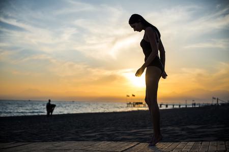 beautiful tan woman in bikini walking on the beach admiring sunset