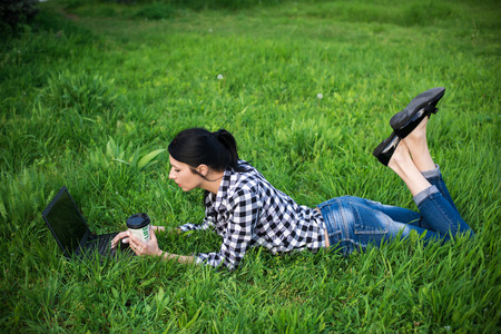 Attractive young woman is lying on grass near a university. She is drinking coffee and relaxing. Banco de Imagens