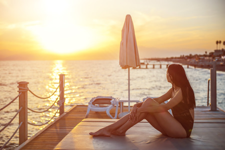 beautiful tan woman in bikini on the pier admiring sunset