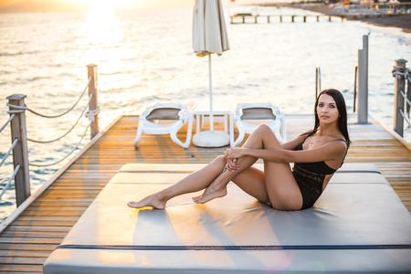 beautiful tan woman in bikini on the pier admiring sunset