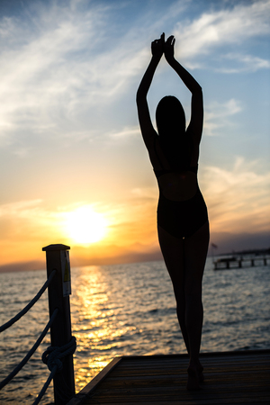 beautiful tan woman in bikini on the pier admiring sunset.