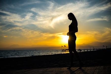 beautiful tan woman in bikini walking on the beach admiring sunset. Standard-Bild