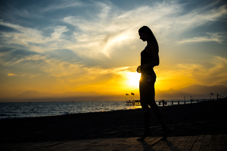 beautiful tan woman in bikini walking on the beach admiring sunset. Stock Photo