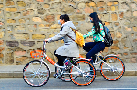 Beijing,China-December 2016-Two girls wearing masks, riding  Mobike  bicycles through the front wall. Editorial