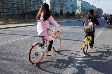 Beijing,China-February 2017-two girl ridding on sharing bicycles in Beijing of china. Stock Photo - 73386386