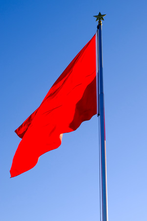 Red flag fluttering in the wind 写真素材