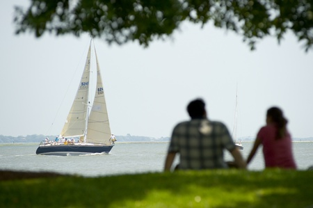 couple sitting in grass at waterfront park to watch regatta in Charleston SC