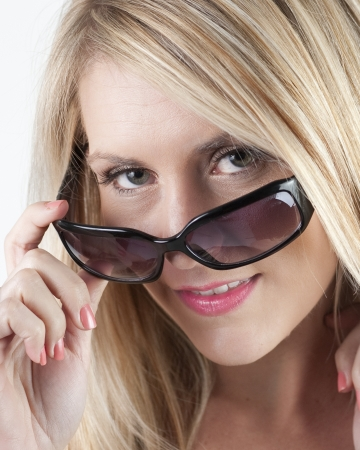 female model looking over the rim of a pair of sunglasses to signal she is attentive
