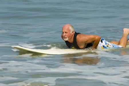 Senior man on Surfboard at Cocoa Beach Florida photo