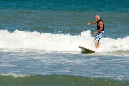 Over 50 year old surfer in Atlantic Ocean at Cocoa Beach Florida