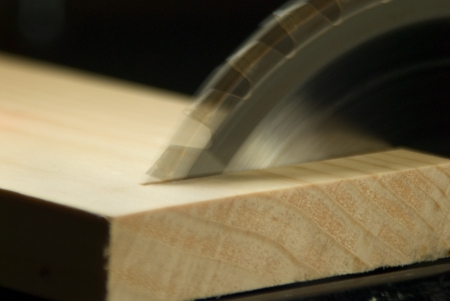 Circular Saw blade making a Cross Cut through a board Stock Photo