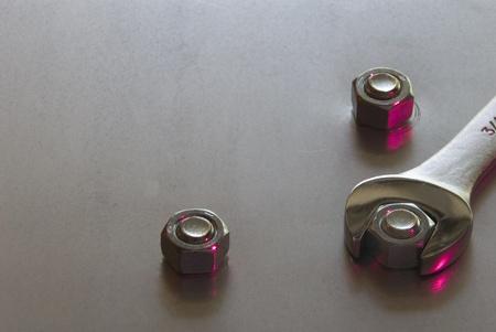 改善を象徴する金属のシート上の 3 つのナットを締付オープンのエンド レンチ