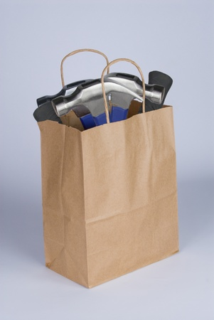A shopping bag containing hammers to represent the statement  dumber than a bag of hammers   Stock Photo